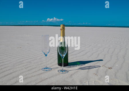A champagne bottle built on the beach, white sand and blue sea is a holiday in paradise. - Stock Photo