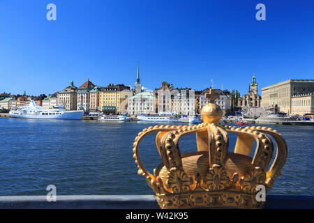 Scenic view of Stockholm's Old Town (Gamla Stan) skyline with the royal golden crown on the foreground, Sweden - Stock Photo