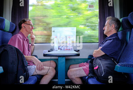 Two older males sitting in train, facing each other while train in motion with visible outside trees in motion blur in windows.  Hungary, - Stock Photo