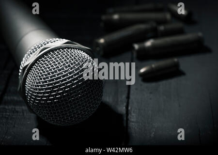 closeup of a microphone on a dark gray rustic surface and some bullets and bullet shells in the background