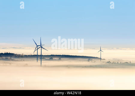 Wind turbines in morning fog Stock Photo