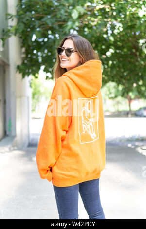 City portrait of positive young female wearing casual clothes orange. Grey background - Stock Photo
