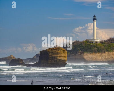 Beach with surf waves and lighthouse in sun, Biarritz France - Stock Photo