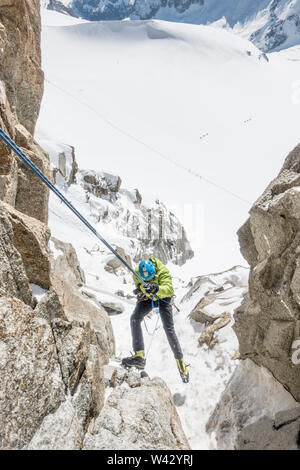 An alpinist is on rappel in steep terrain high above a French glacier - Stock Photo