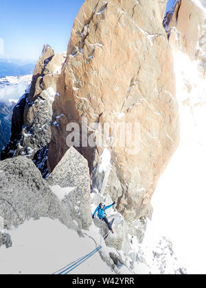 Woman alpinist flashes victory sign while on rappel in the French Alps - Stock Photo