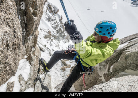 Alpinist rappelling steep terrain high above a Mont Blanc glacier - Stock Photo