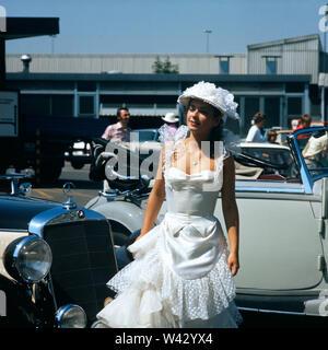 Eine junge Frau in einem weißen Kleid steht zwischen zwei Oldtimern auf einer Autoshow in München in den 1980er Jahren.  A young woman in a white dress stands between two classic cars at a car show in Munich in the 1980s. - Stock Photo