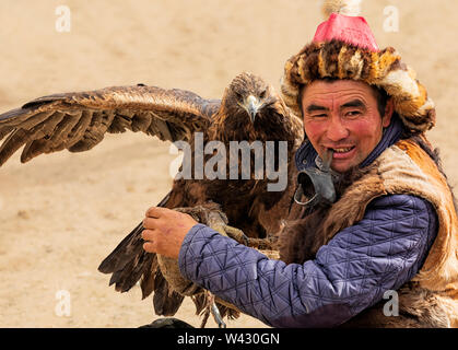 Bayan-Ulgii, Western Mongolia - October 07, 2018: Nomad Games, Golden Eagle Festival. Sunny Day. Mongolian Hunter is sitting With Golden Eagle On hand - Stock Photo