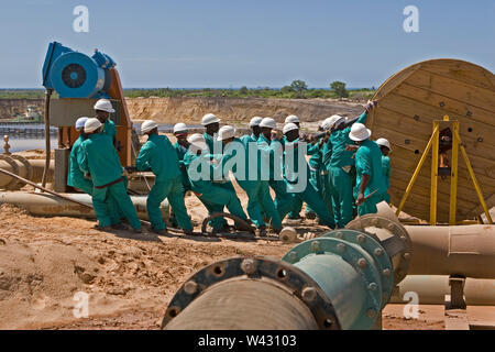 Mining, managing & transporting of titanium mineral sands. Maintenance team laying new power cables at the side of mining pond for wet plant behind. - Stock Photo