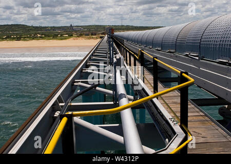 Mining, managing & transporting of titanium mineral sands. 400m long jetty supporting end of 2.4km overland covered conveyor and pedestrian walkway. - Stock Photo
