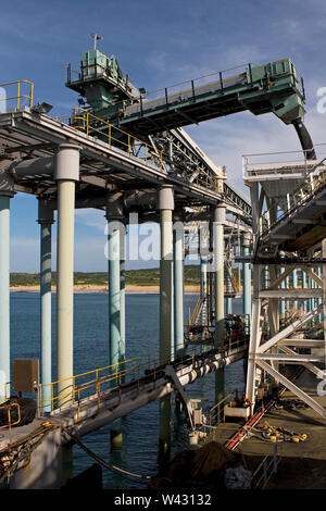 Mining, managing & transporting of titanium mineral sands. From floating jetty up to main one loading product into barge via boom & 'elephant trunk'. - Stock Photo