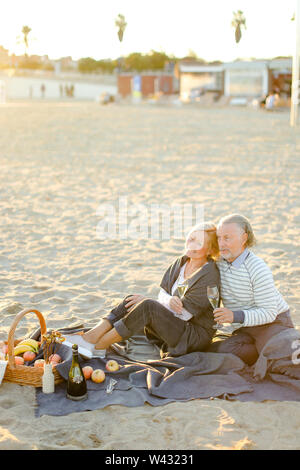 Two pensioners sitting on plaid on sand beach with champagne and fruits. Concept of elderly couple on picnic. - Stock Photo
