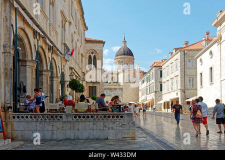 Pred Dvorom; pedestrian street; shiny surface; Rector's Palace; Cathedral tower; outdoor restaurant, people, Old town; Dubrovnik; Croatia; Europe; sum - Stock Photo