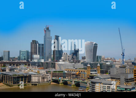 City of London, United Kingdom 6th July 2019: London skyline seen from south bank, river Thames in foreground on summer day - Stock Photo