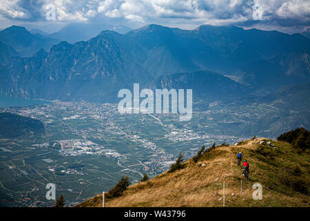 Two mountain bikers riding a narrow grassy trail on a ridgeline with Riva del Garda and dramatic clouds and mou - Stock Photo