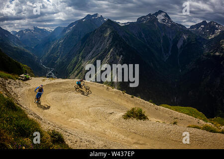 Two mountain bikers riding a 'bermed' corner on a bike-park trail, with a steep river valley and dramatic alpine peaks - Stock Photo