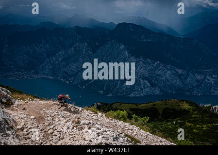 A mountain biker riding a corner on a dangerous rocky trail high above Lake Garda with dark dramatic mountains and storm clouds - Stock Photo