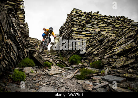 A mountain biker riding on a rocky mining path between ancient dry-stone walls.