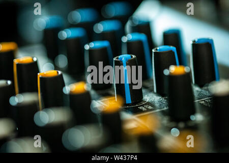 Close-up of volume and tone control knobs on an audio mixing desk - Stock Photo