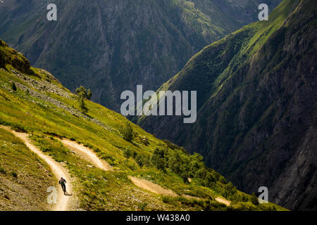 A mountain biker riding a 'bermed' corner on a bike-park trail, with a steep river valley and dramatic valley behind. - Stock Photo