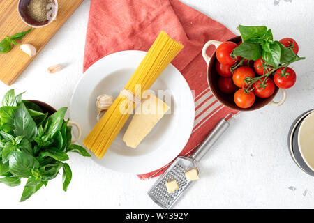 Raw Italian pasta with ingredients for cooking spaghetti on a white background top view - Stock Photo