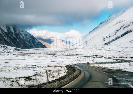 Georgian military road. The scenic winding road among the mountains in Georgia. Main Caucasian Ridge and Cross Pass Gudauri in winter. - Stock Photo