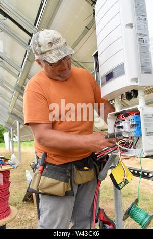 Certified electricians installing a solar electric (photovoltaic) system in a field to generate electricity from the sunlight, Wisconsin, USA - Stock Photo