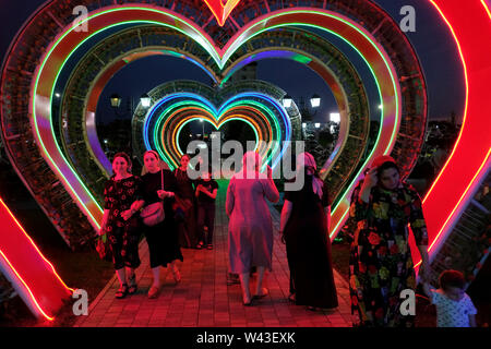 Chechen women walking at night through an illuminated heart-shaped tunnel in Tsvetochny or flower park in the center of Grozny the capital city of Chechnya officially the Chechen Republic in the North Caucasian Federal District of Russia. - Stock Photo