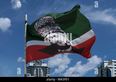 The Chechen flag bearing the image of Akhmad Kadyrov former Head of the Chechen Republic fluttering in Grozny the capital city of Chechnya in the North Caucasian Federal District of Russia. - Stock Photo
