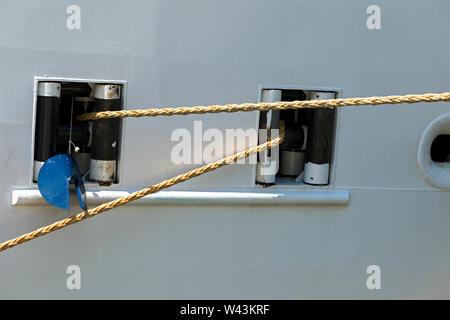 Cruise ships mooring ropes with blue rat guard hanging. Closeup. Stock Image