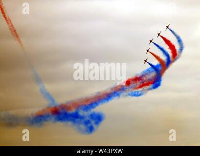 The RAF Red Arrows BAE systems Hawk display team leaving trails of colourful red and blue contrails in the sky above Swansea bay, Wales, UK. - Stock Photo