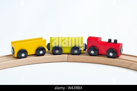 Wooden toy train with colorful blocks on a wooden railway. Educational toys. - Stock Photo