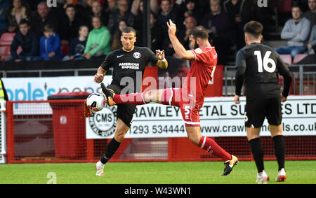 Crawley Sussex, UK. 19th July, 2019. Brighton's Tomer Hemed tries to win the ball as he is challenged by Joe McNerney of Crawley during the pre season friendly football match between Crawley Town and Brighton and Hove Albion at the People's Pension Stadium in Crawley . Credit: Simon Dack/Alamy Live News Stock Photo