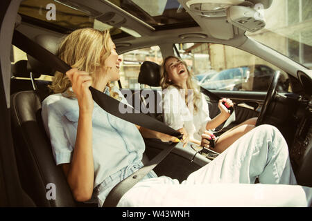 Young lesbian's couple preparing for vacation trip on the car in sunny day. Women sitting and ready for going to sea, riverside or ocean. Concept of relationship, love, summer, weekend, honeymoon. - Stock Photo