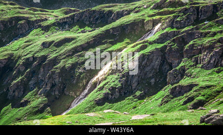 Panoramic view of a small river passing through mountains green meadows. Summer in the Pennine Alps, Valle d'Aosta, Italy, Europe. - Stock Photo