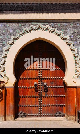 Morocco, Fez. Beautiful facade and Arabesque arched doorway and glazed tile door-surround with Islamic symmetrical patterns in the old medina. UNESCO - Stock Photo