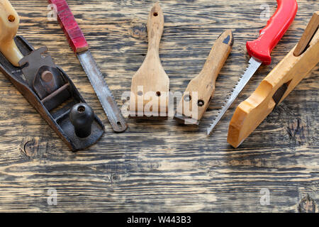 Old carpentry tools, planers, handsaws and cycles lie on a wooden table. - Stock Photo
