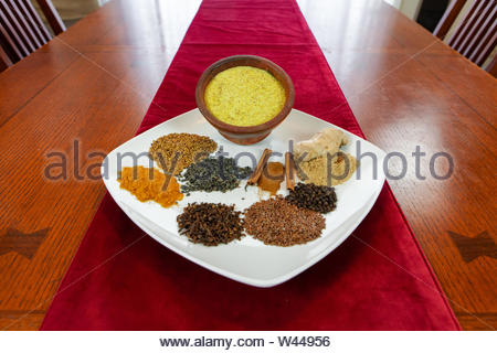 Colorful spices and powdered bsissa presented neatly on a ceramic serving plate. Raw ingredients used in bsissa pudding recipes. Cultural food from North Africa - Stock Photo