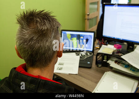 A closeup view on the back of a man's head sitting at office desk. Person focused on laptop screen with papers on desk. Office work environment. - Stock Photo