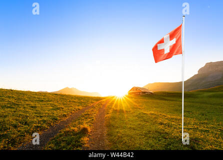 small road leading to a swiss chalet or farm in a mountain landscape at sunrise with sun star and a waving swiss flag in the foreground - Stock Photo