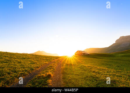 small road leading to a swiss chalet or farm in a mountain landscape at sunrise with sun star - Stock Photo