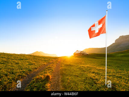 small road leading to a swiss chalet or farm in a mountain landscape at sunrise with circular sun glow and a waving swiss flag in the foreground - Stock Photo