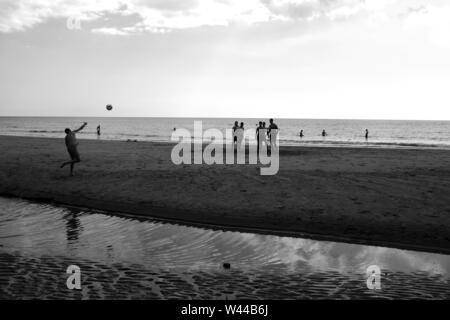 A group of young men playing football on the sandy beach at low tide. One of them is throwing the ball for the others - Stock Photo
