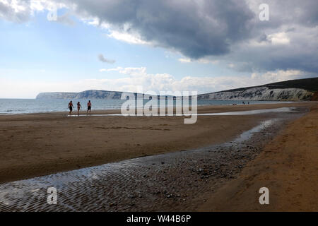 A group of friends exiting the sea from a swim at low tide on the sandy beach shoreline on Compton Beach, Compton Bay, on the Isle of Wight - Stock Photo