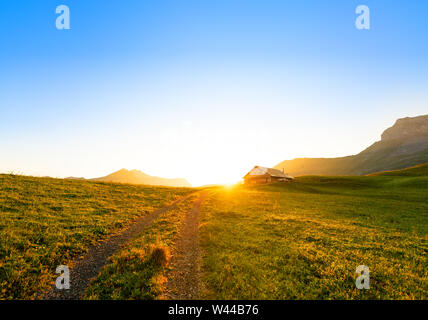 small road leading to a swiss chalet or farm in a mountain landscape at sunrise with circular sun glow - Stock Photo