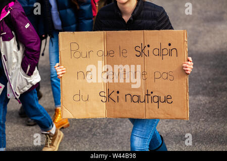 A closeup view of a homemade French sign, saying so that alpine skiing does not become water skiing, held by an environmentalist as protestors march for climate - Stock Photo