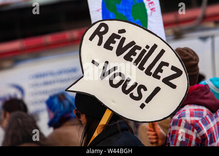 A closeup view of a homemade French poster, saying wake up, held by eco-activists during a city march against climate change - Stock Photo
