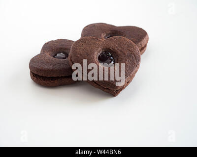 A heart-shaped chocolate cookie sandwich with a layer of jam between the two chocolate cookie layers - Stock Photo