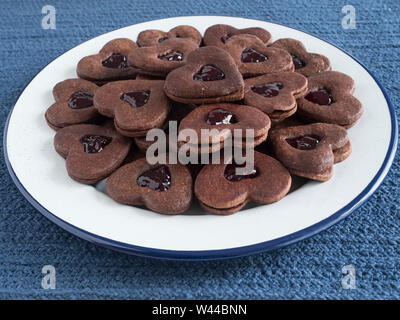 A plate of heart-shaped chocolate sandwich cookies with a layer of jam between the two chocolate cookie layers on a blue and white plate, against a bl - Stock Photo