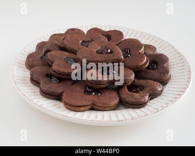 A plate of heart-shaped chocolate sandwich cookies  with a layer of jam between the two chocolate cookie layers - Stock Photo